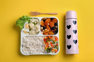 Thermos and lunch box with food on yellow background, flat lay