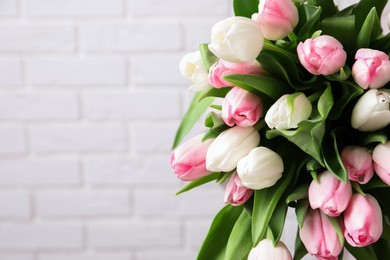 Beautiful bouquet of tulips against white brick wall. Space for text