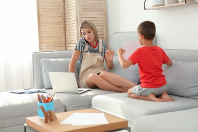 Little boy bothering mother at work in living room. Home office concept