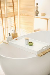 Scented candles on tray for tub in bathroom. Interior design