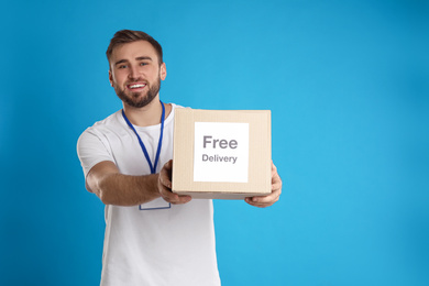Male courier holding parcel with sticker Free Delivery on light blue background
