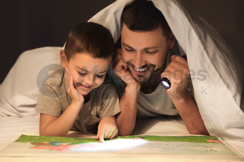 Father and son with flashlight reading book under blanket at home