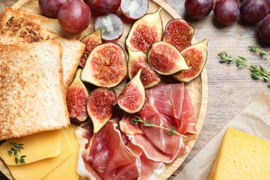 Delicious ripe figs, prosciutto and cheese served on wooden table, flat lay