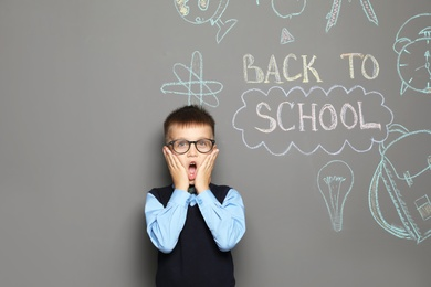 Little child in uniform near drawings with text BACK TO SCHOOL on grey background