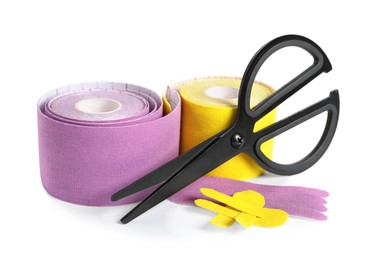 Scissors, bright kinesio tape rolls and pieces on white background