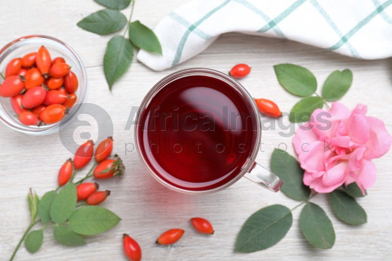 Flat lay composition with aromatic rose hip tea on white wooden table