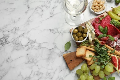 Set of different delicious appetizers served on white marble table, flat lay. Space for text