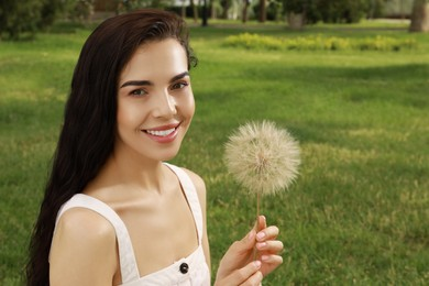 Beautiful young woman with large dandelion in park, space for text. Allergy free concept