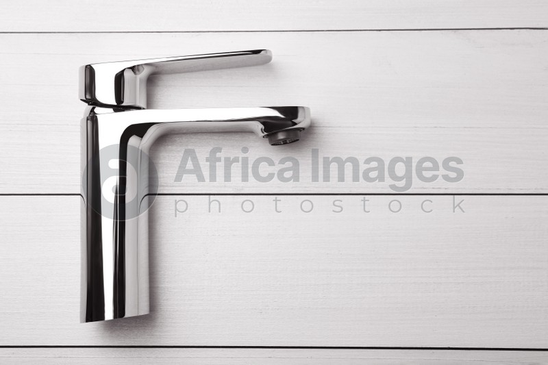 Single handle water tap on white wooden table, top view. Space for text