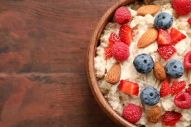 Tasty oatmeal porridge with berries and almond nuts in bowl on wooden table, top view. Space for text