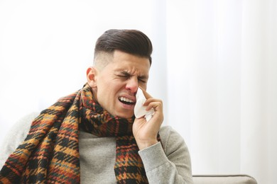 Ill man with scarf suffering from head cold at home