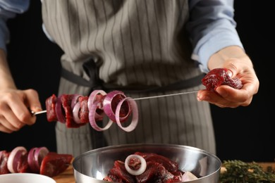 Woman stringing marinated meat on skewer at table, closeup
