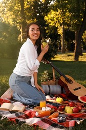 Happy young woman having picnic on plaid in summer park