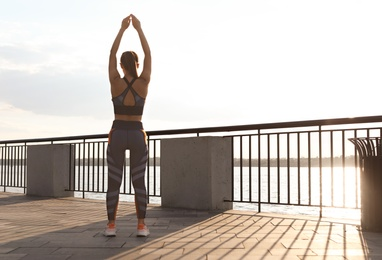 Young woman stretching on pier near river in morning, back view. Space for text