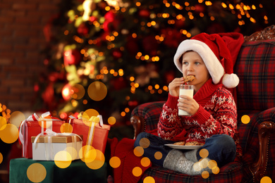 Little boy in Santa Claus cap with milk and cookies near Christmas gifts at home