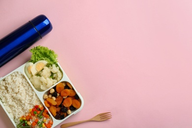Thermos and lunch box with food on pink background, flat lay. Space for text