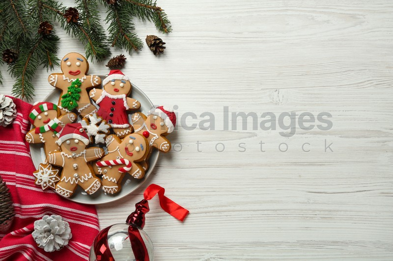 Delicious Christmas cookies and festive decor on white wooden table, flat lay. Space for text