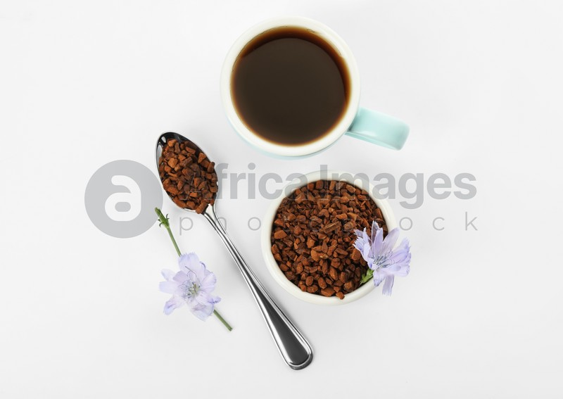 Cup of delicious chicory drink, granules and flowers on white background, top view