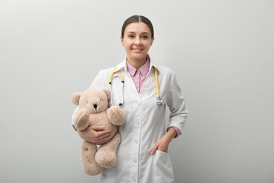 Pediatrician with teddy bear and stethoscope on light grey background