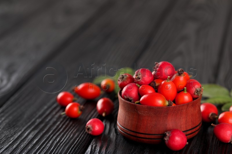 Ripe rose hip berries with green leaves on black wooden table. Space for text