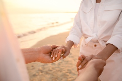 Lovely couple holding hands on beach at sunset, closeup