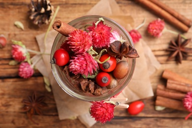 Aromatic potpourri in glass jar on wooden background, flat lay