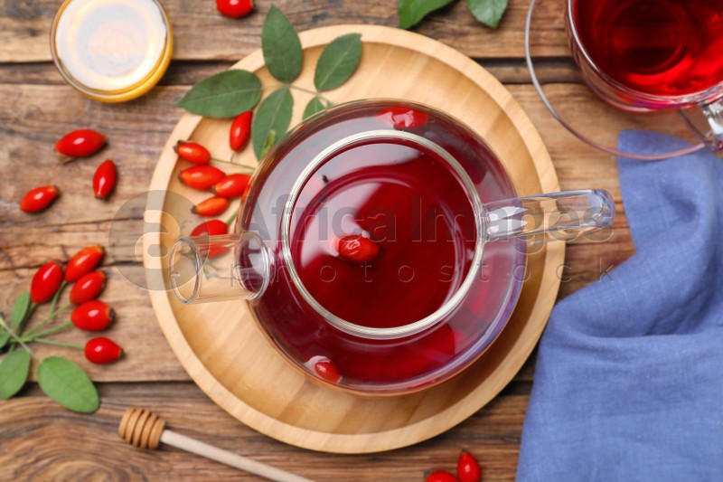 Flat lay composition with aromatic rose hip tea on wooden table