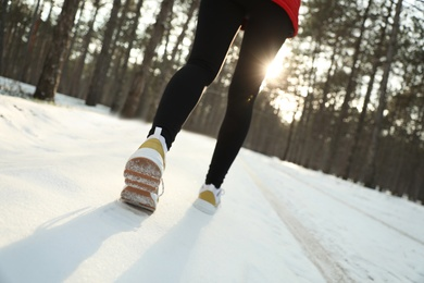 Woman running in winter forest, closeup. Outdoors sports exercises