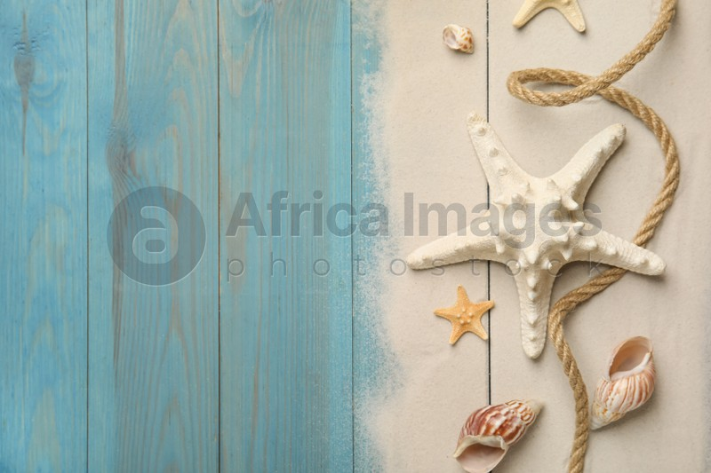 Beautiful sea stars, shells, rope and sand on blue wooden background, flat lay. Space for text