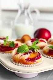 Delicious cupcakes with plums in baking pan, closeup