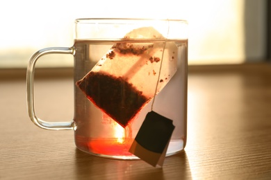 Tea bag in cup of hot water on wooden table, closeup