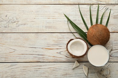 Delicious vegan milk and coconuts on white wooden table, flat lay. Space for text