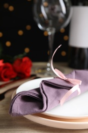 Beautiful place setting for romantic dinner on table against black background with blurred lights, closeup. Valentine's day celebration