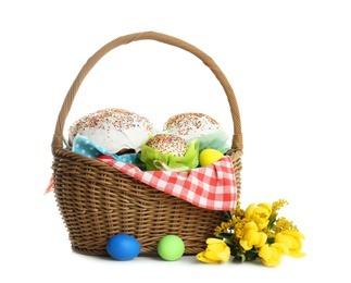 Basket with delicious Easter cakes, dyed eggs and flowers on white background