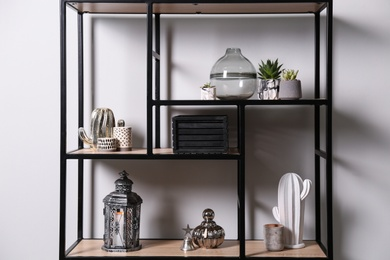 Shelving with different decor and houseplants near white wall. Interior design