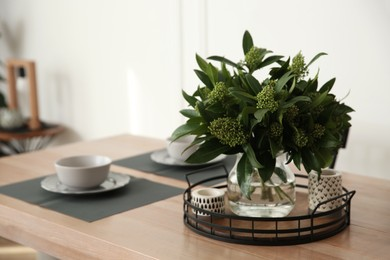 Fresh bouquet on dining table in room, closeup. Interior design