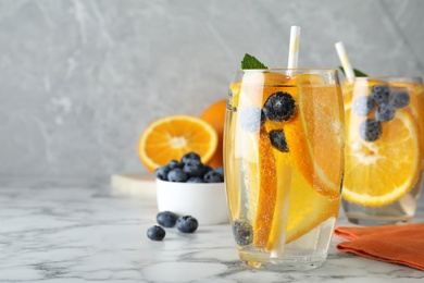 Delicious orange lemonade with soda water, mint and blueberries on white marble table, space for text. Fresh summer cocktail