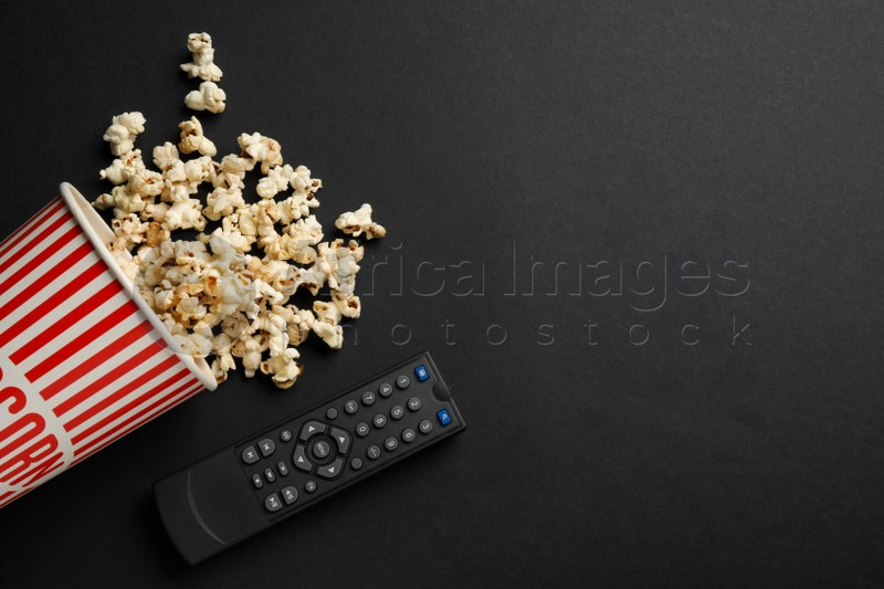 Modern tv remote control and popcorn on black background, flat lay. Space for text