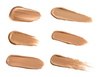 Set with different shades of liquid skin foundation on white background, top view
