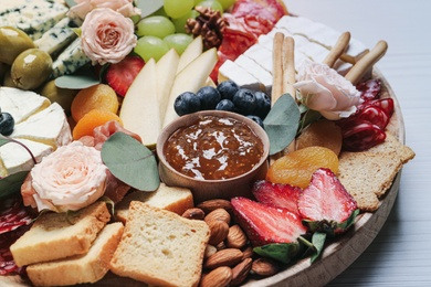Wooden plate full of assorted appetizers on table, closeup