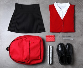 Flat lay composition with school uniform on grey stone background