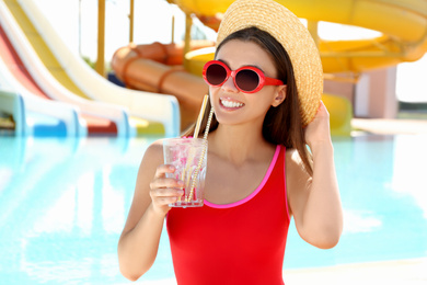 Woman with glass of refreshing drink in water park