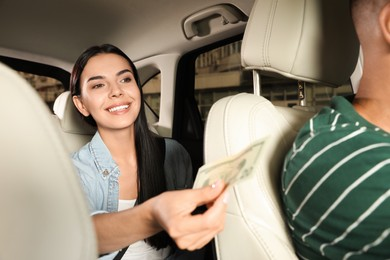 Young woman giving money to taxi driver in modern car
