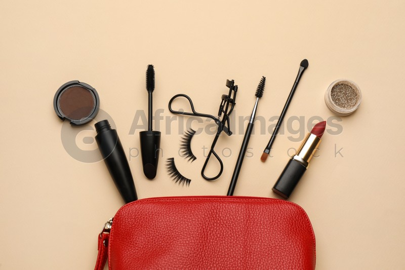Cosmetic bag with eyelash curler and makeup products on beige background, flat lay