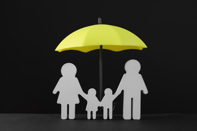 Small umbrella and family figure on black background