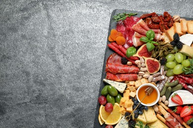 Set of different delicious appetizers served on grey table, top view. Space for text