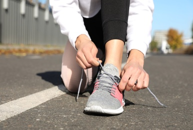 Sporty woman tying shoelaces outdoors on sunny morning, closeup