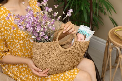 Woman holding beach bag with beautiful bouquet of wildflowers and magazine indoors, closeup