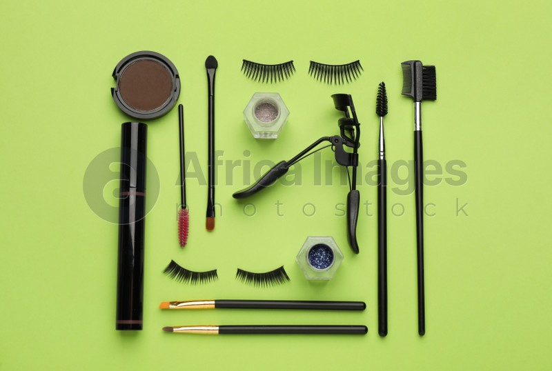 Flat lay composition with eyelash curler, makeup products and accessories on light green background