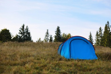 Blue camping tent on green grass near forest, space for text